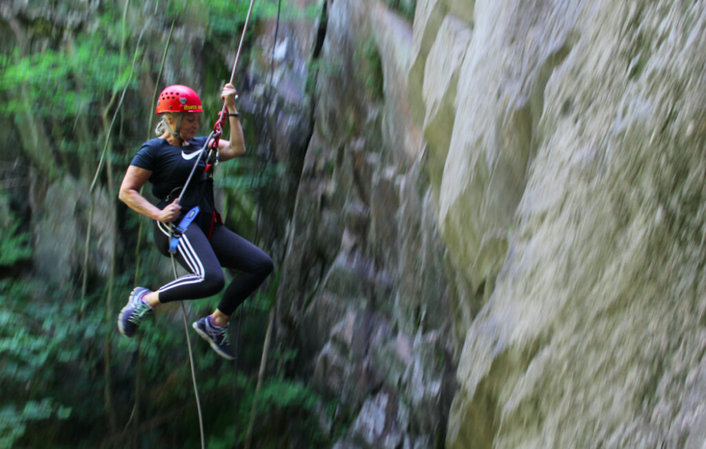 Woman abseiling down cliff in the Lake District