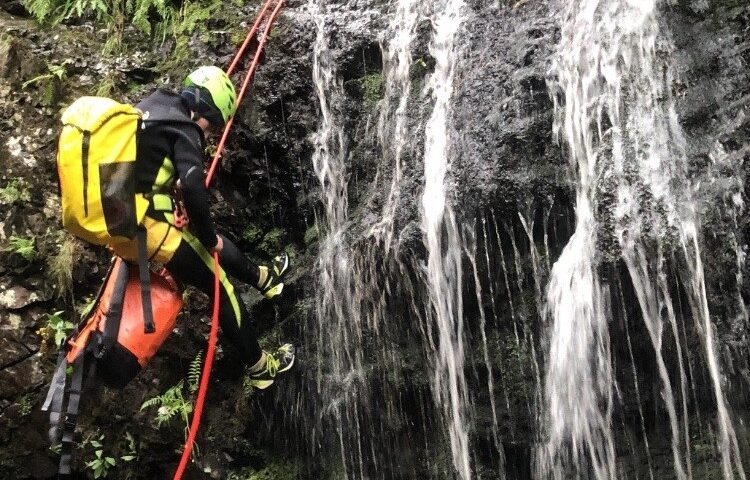 Keswick Adventures abseiling down a waterfall while canyoning