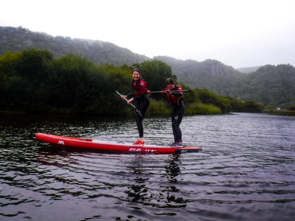 Teenagers paddle boarding in the Lake District