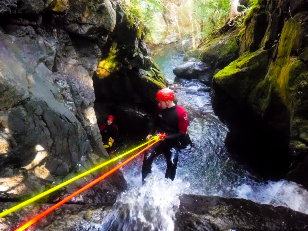 Abseiling down a waterfall during canyoning