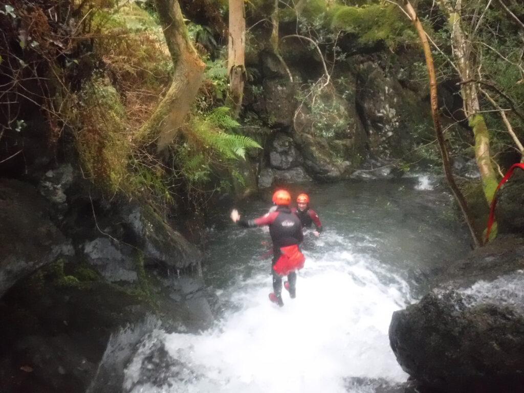 Jumping over a waterfall during ghyll scrambling near Keswick
