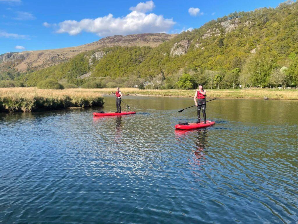 Couple paddle boarding on a river near Keswick
