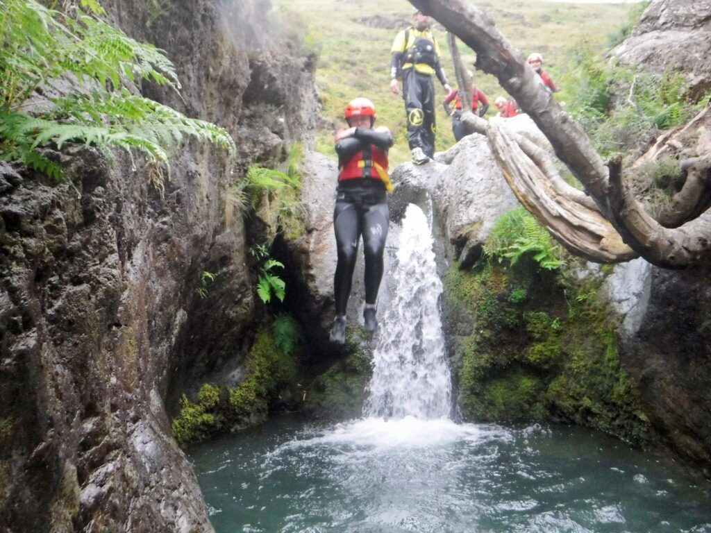 Person jumping of a waterfall in the Lake District
