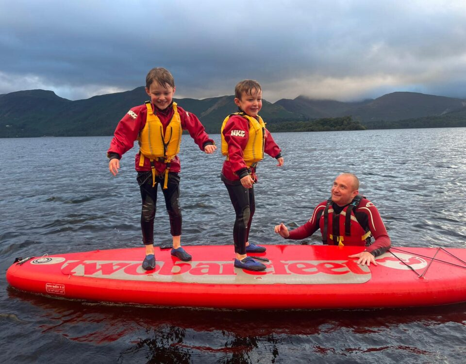 Family of two boys and a dad on a paddle board in the Lake District